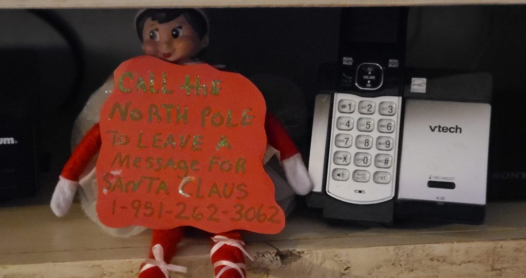 elf on the shelf sitting by the phone