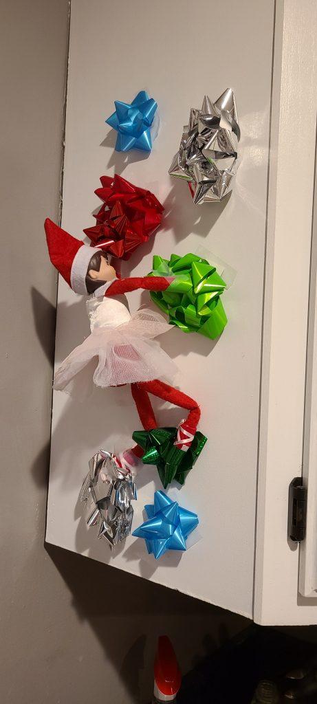 Elf on the shelf climbing up bows