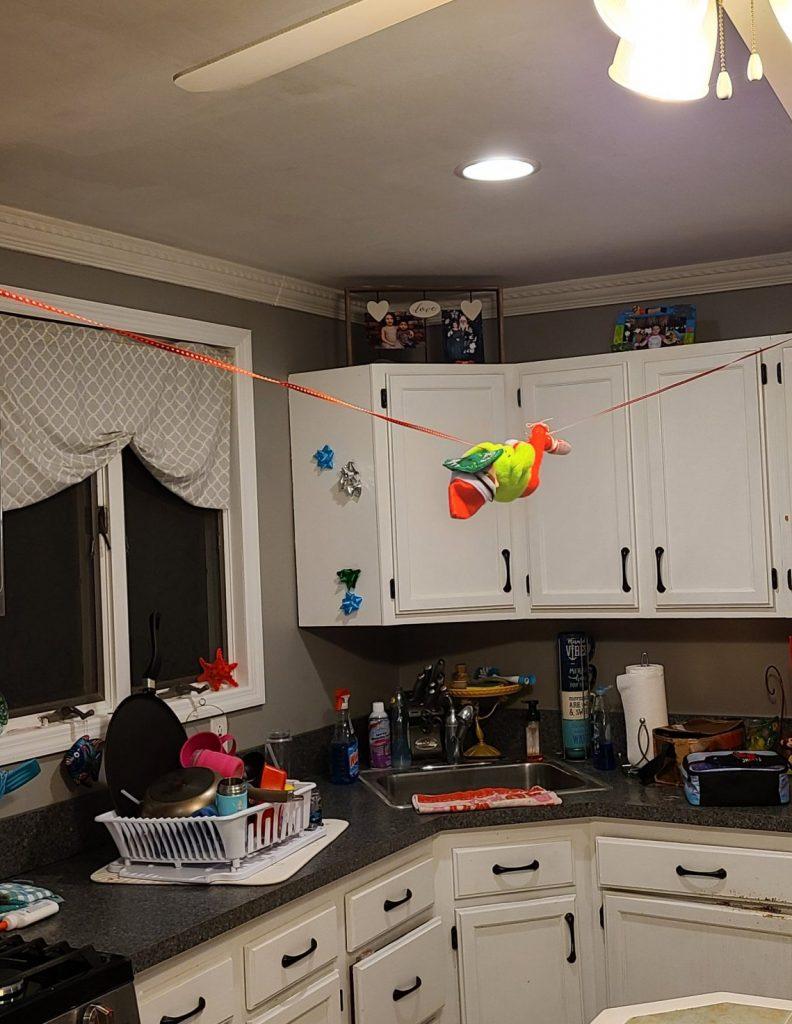 Elf on the Shelf ziplining through the kitchen